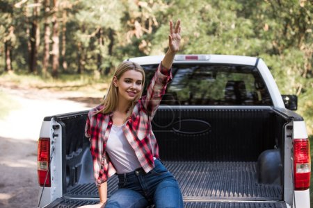 happy blonde girl waving and sitting on pickup truck in forest