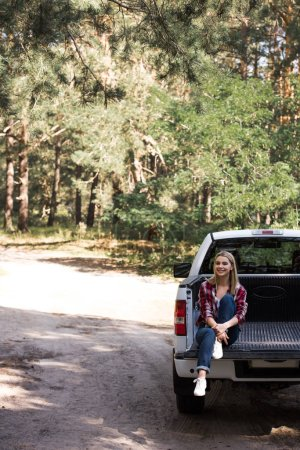 Photo for Happy young woman sitting on pickup truck in forest - Royalty Free Image