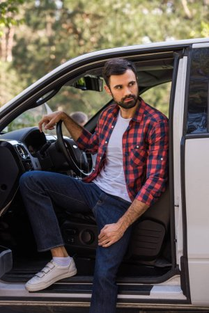 Photo for Handsome bearded driver sitting in pickup truck in forest - Royalty Free Image