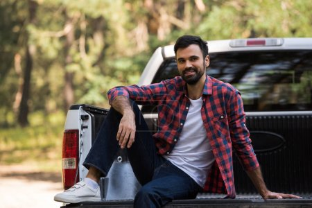 smiling bearded man sitting on white pickup truck in forest