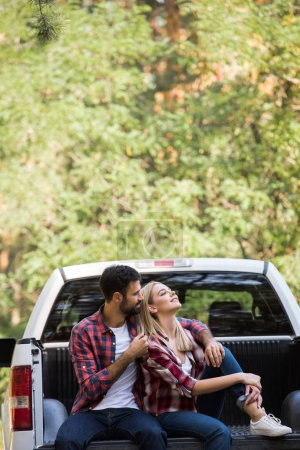couple sitting together on pickup truck in forest