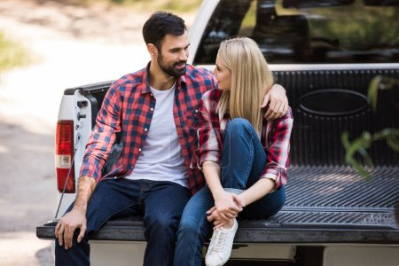 young couple hugging on pickup truck and looking at each other