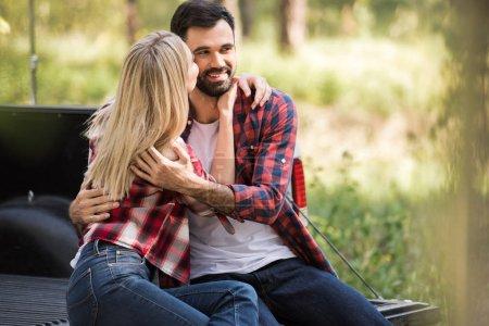 blonde girl kissing cheek of smiling boyfriend while sitting on pickup truck