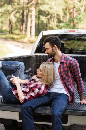 happy couple resting on pickup truck in forest