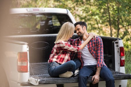 beautiful couple sitting on pickup truck and looking at each other in forest