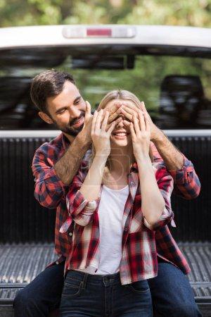 handsome boyfriend closing eyes of happy girlfriend near car