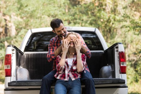 smiling man closing eyes of happy girlfriend while sitting on pickup truck