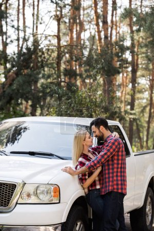 beautiful couple going to kiss near pickup truck in forest