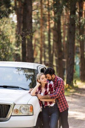 handsome boyfriend hugging his girlfriend near pickup truck in forest