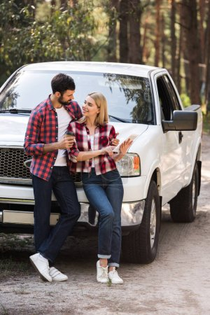couple using digital tablet and looking at each other near pickup truck in forest