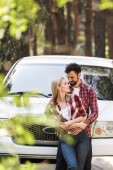 beautiful smiling couple embracing near white pickup truck