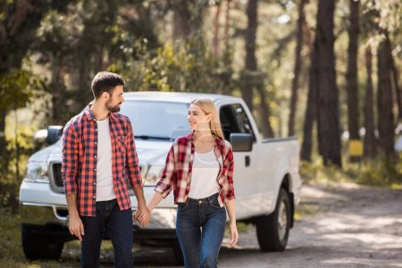 young couple holding hands and walking in forest with pickup truck