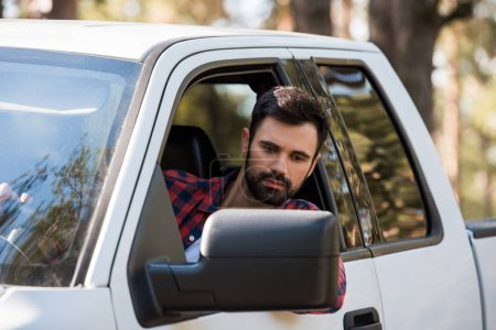 handsome bearded man driving pickup truck in forest
