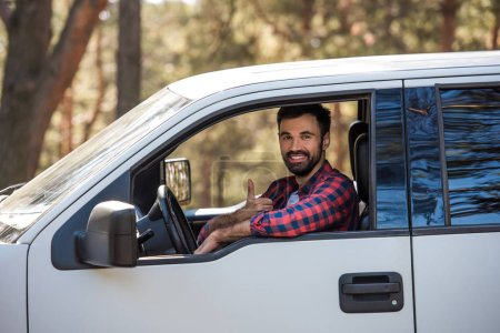 bearded driver showing thumb up while sitting in pickup truck in forest