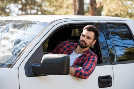 Photo for Serious bearded man driving pickup truck in forest - Royalty Free Image