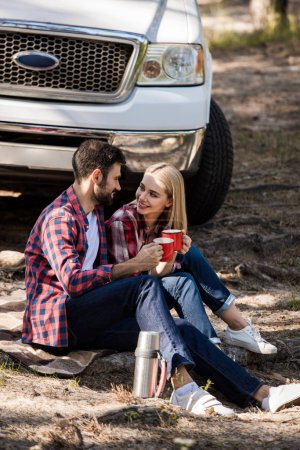 smiling couple having picnic with hot drink on blanket near pickup truck