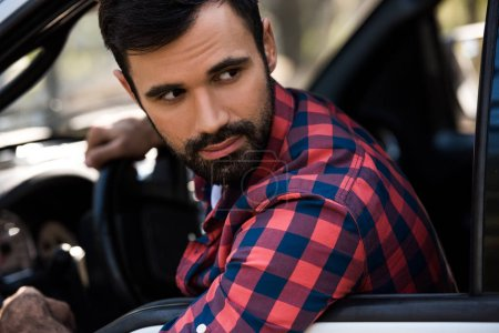 handsome bearded man driving pickup truck