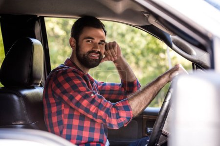 smiling bearded man driving pickup truck in forest
