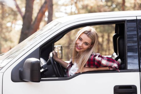 beautiful young driver sitting in pickup truck in forest