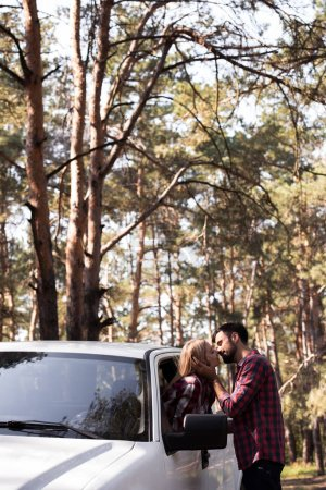 man kissing girlfriend while she sitting in pickup truck in forest