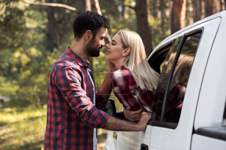happy boyfriend going to kiss smiling girlfriend while she sitting in pickup truck