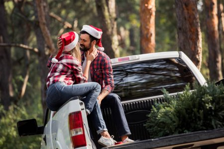 couple in santa hats going to kiss while sitting on pickup truck with fir tree for christmas in forest