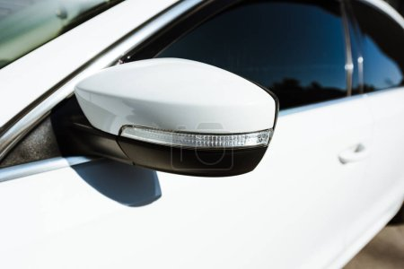 close up of side mirror of white new car on street
