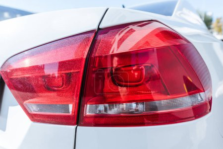 close up of red rear headlight of white new car on street