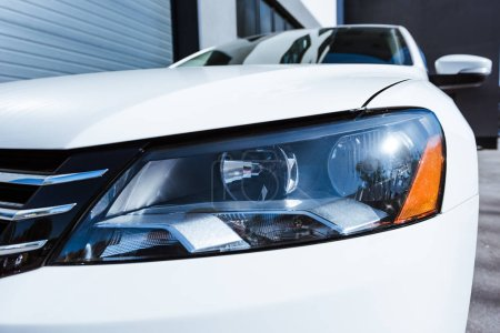 close up of headlight of white new car on street
