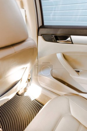 cropped image of new car with beige leather interior and sunlight