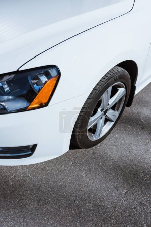 cropped image of headlight and wheel of white new car on road