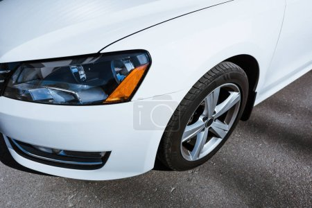 cropped image of headlight and wheel of white new car on street