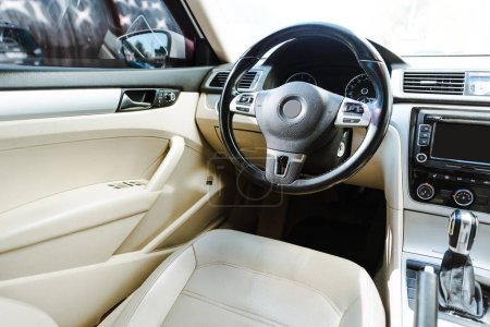 cropped image of black steering wheel and beige leather seats new car on street