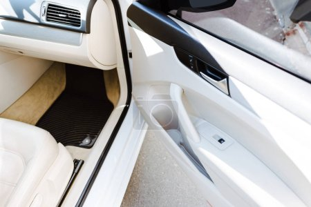 cropped image of open door of new car on street