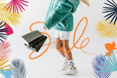 cropped view of girl in turquoise fur coat holding black shopping bags on white, sale banner concept