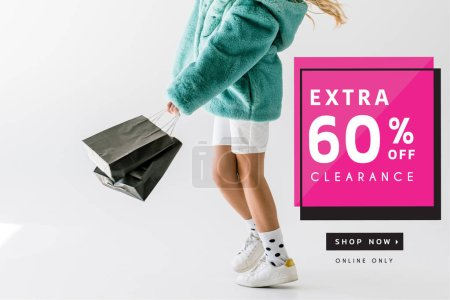 cropped view of girl in turquoise fur coat holding black shopping bags on white, extra clearance banner