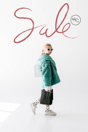 Photo for Fashionable shopaholic in fur coat and sunglasses posing with black shopping bags on white, sale inscription - Royalty Free Image