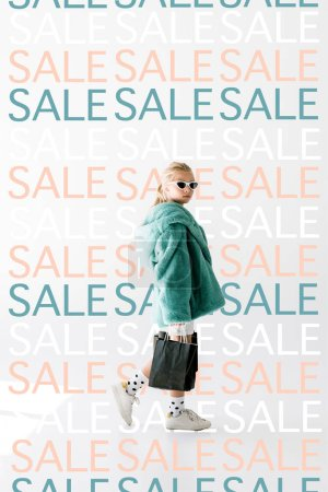fashionable shopaholic in fur coat and sunglasses posing with black shopping bags on white, repetition of sale signs