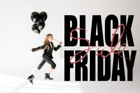 fashionable child in trendy suit jumping with black balloons on grey, black friday banner concept