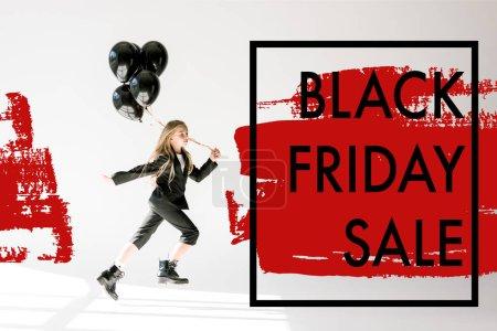 Photo pour Enfant à la mode en combinaison à la mode sautant avec des ballons noirs sur gris, concept de bannière de vente vendredi noir - image libre de droit