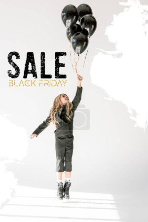 dreamy child jumping or flying with black balloons on grey, black friday sale banner concept