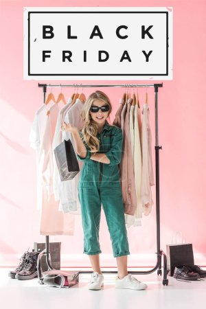 stylish child in overalls and sunglasses standing with shopping bag near clothes and footwear in boutique, black friday sale banner concept