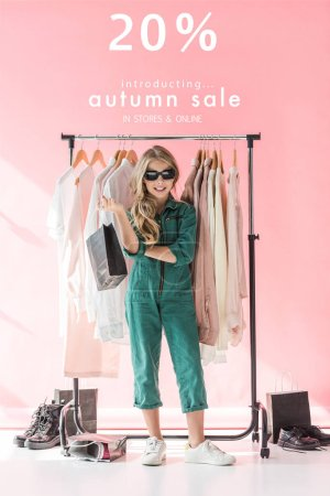 Photo for Stylish child in overalls and sunglasses standing with shopping bag near clothes and footwear in boutique, autumn sale banner concept - Royalty Free Image