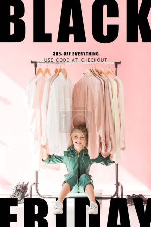 Photo for Cheerful charming kid in trendy overalls sitting under clothes on hangers, black friday sale banner - Royalty Free Image