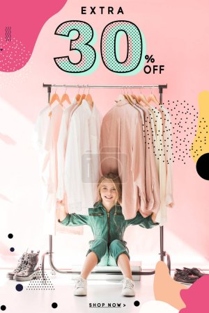 cheerful charming kid in trendy overalls sitting under clothes on hangers, sale banner concept