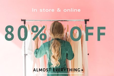 Photo for Rear view of blonde kid in trendy overalls choosing clothes on hangers, sale banner concept - Royalty Free Image