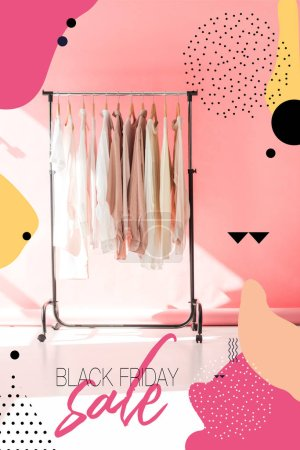 light stylish clothes on hangers in pink boutique, black friday sale banner concept