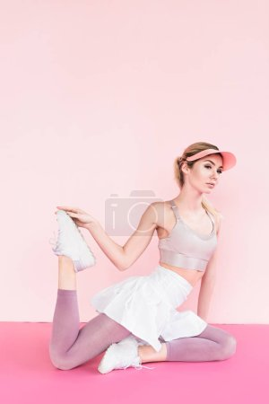 stylish attractive sportswoman in visor hat exercising on pink