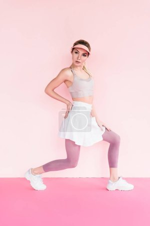 attractive stylish sportswoman in visor hat doing exercise on pink