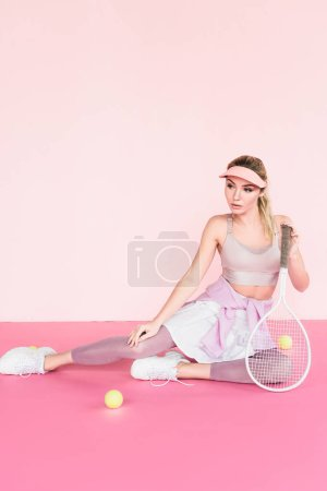 sportswoman in visor hat posing with tennis racket and balls on pink